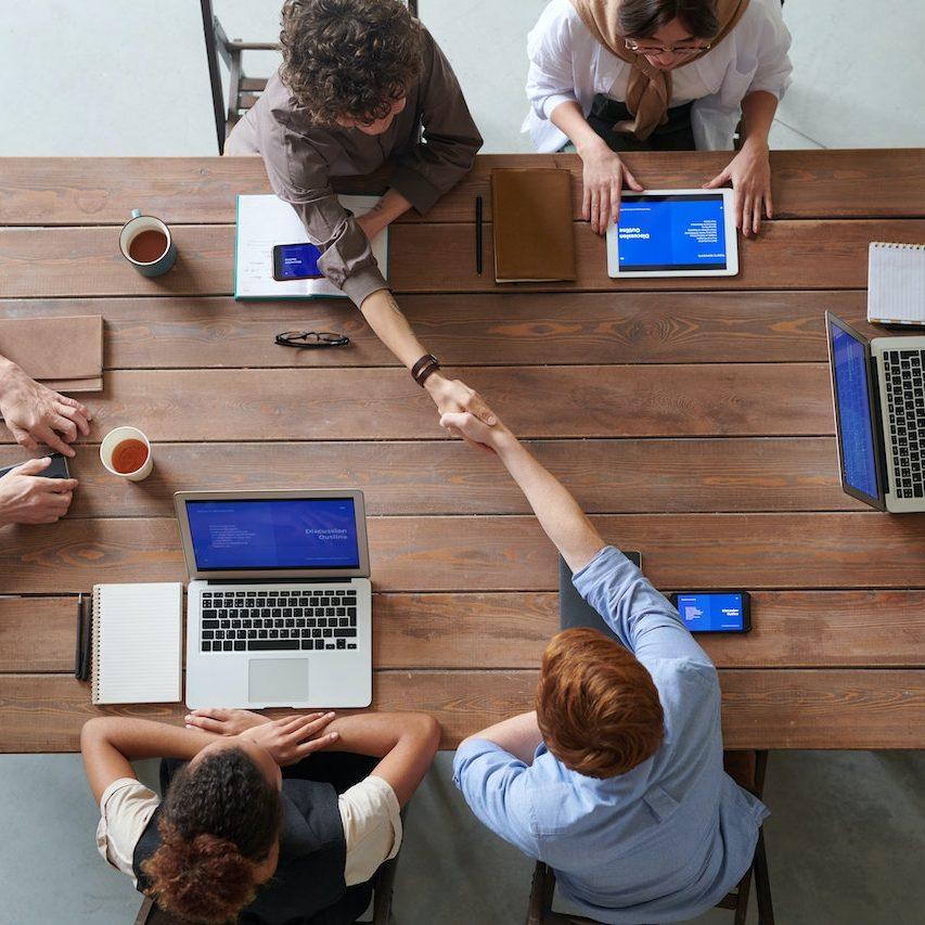 branchenlösungen_individuelle Lösungen besprechen Menschen mit Notebooks am Tisch_zwei geben sich die Hände