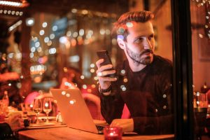Mann sitzt im Restaurant mit Smartphone in der Hand Gästeregistrierung für Gastronomie Hotel und Handel